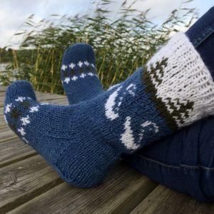 Fötter med stickade sockor på en bryfgga med vass i bakgrunden.