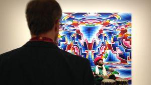 ryggen av Alvar Gullichsen på vernissage i galleri i Helsingfors, trummare i bakgrunden