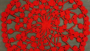 Julgransmatta gjord av rött elefantgarn.