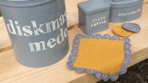 Plåtburkar med text, krokad disktrasa och virkade tvättlappar på en bänk utomhus.