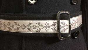 Kappa emd bälte som har reflex med ritat korsstygnsmönster
