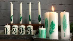 Olika sorters vita ljus med gröna mönster av siffror, fjädrar och granris