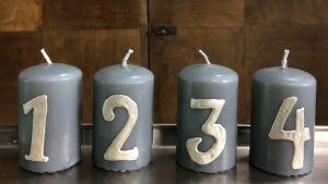 Fyra gråa blockljus med siffrorna 1-4 i vitt
