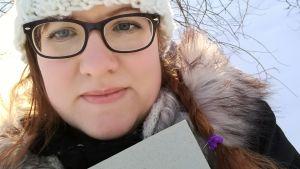 Kirjabloggaaja Heidi P. Kari Hotakaisen kirja Juoksuhaudantie kädessään