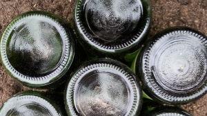 Strampsten av sju flaskor som är nergrävda som en bunt med bottnarna upp