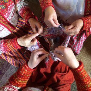 Tre personers händer som stickar på samma tröja samtidigt.