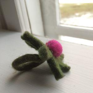 En grön tovad ring med en lila boll