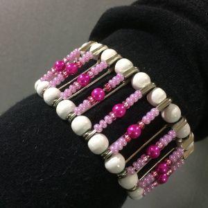 Arm med ett armband gjjort av säkerhetsnålar och pärlor.