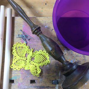 rundstav, skruvar, virkad duk, ljusstake och plasthink på en bänk.
