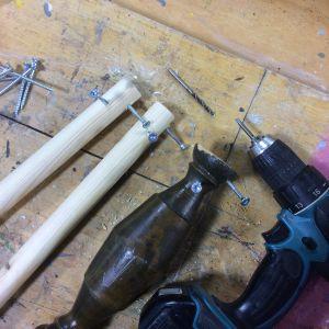 Skruvdragare och träben med skruvar på en bänk