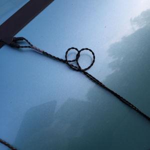 Auton konepellillä kuulokejohto, jossa itsestään syntynyt sydämen mallinen löysä solmu.