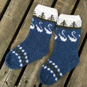 Stickade sockor i blått med vita svanar och gröna granar.