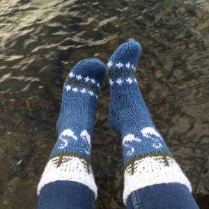 Fötter iklädda stickade sockor och vatten i bakgrunden.