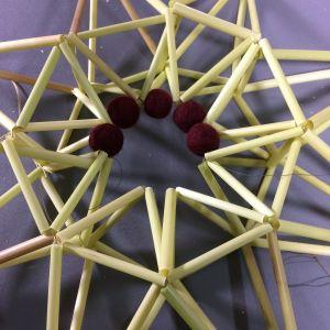 vassrör formade till en stjärna med yllebollar i mitten.