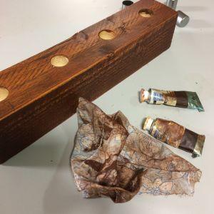 Träbit, färgtuber och trasa som använts för att gnugga in färgen i träet
