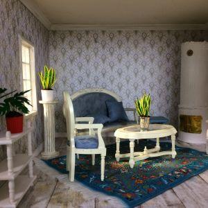 Möblerad salong i ett dockhus.