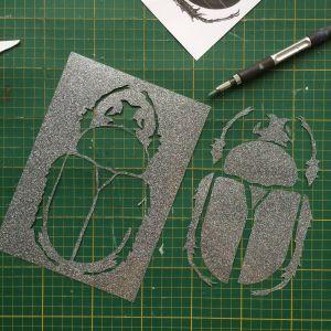 Utskuret mönster av en förstorad skalbagge i glitter