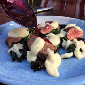 Stekta gräsandsbröst på en bädd av stekt grönkål, med jordärtskockspuré, serverat med lingonreduktion.