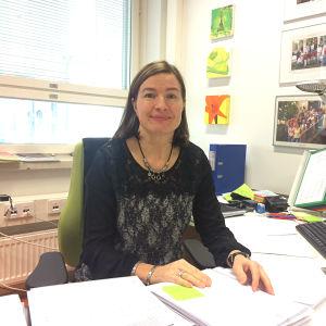 Rektor sitter vid skrivbordet med papper framför sig