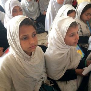 Afghanska flickor i vita huvuddukar undervisas i tältskola