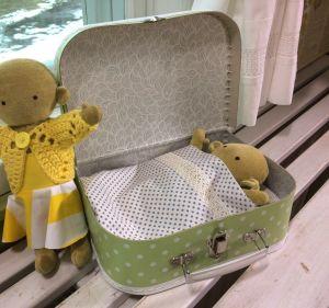 En docka som ligger nerbäddad i en liten kappsäck och en docka som står bredvid, iklädd kjol och virkad kofta.