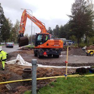 Grävmaskin och gatuarbetare bygger väg.