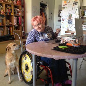 Heljä Hesso leikkaa nettivideoita kotonaan. Late-koira seuraa vierestä.