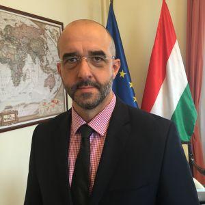 Ungerska preminärministerns talesman Zoltan Kovacs, i bakgrunden en svartvit världskart samt EU:s och Ungerns flaggor.