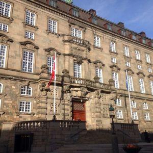Huvudfasaden på danska Folketinget, danska flaggan och blå himmel.