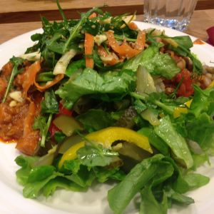 en tallrik fylld med grönsallad, böngryta och ytterlihare en vegansk röra som innehåller bland annat jordnötter.
