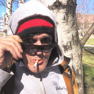 Andy Mc Coy tittar fram bakom sina solglasögon, i munnen har han en cigarett