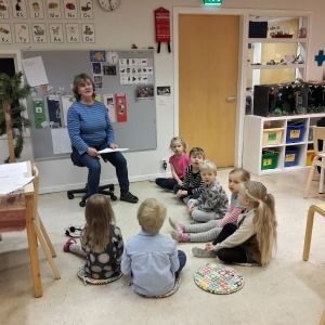 Morgonsamling på språkbadsdaghemmet Sälen. Barnen sitter i halvcirkel runt Marja Rönneberg.