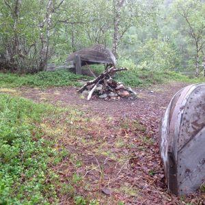 Kaksi puuvenettä kumollaan nuotiopaikan vieressä.