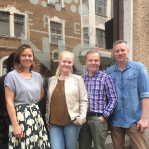 Sonja Kailassaari, Lotta Backlund, Robert Bergholm och Mårten Svartström står på trottoaren utanför redaktionen i centrum