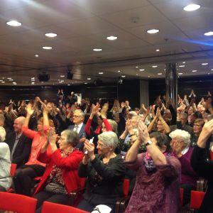 en stor samling pensionärer klappar i händerna i stor sal med röda sitsar