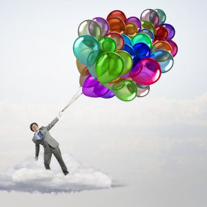 En man håller i ett knippe ballonger.
