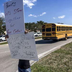 Skolbuss i USA och skylt med protest mot vapen.