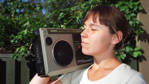 Radion kuuntelija kesällä, matkaradio olkapäällä.