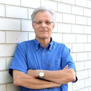 Erik Bonsdorff står iklädd en blå skjorta vid en ljusgrå tegelvägg.