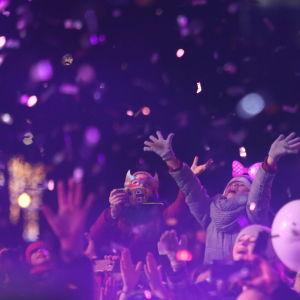 Konfetti och ljusrött ljus över en folkmassa som jublar och klappar i händerna.