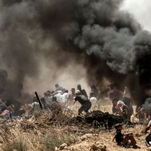 Palestinier i närheten av gränsstängslet mellan Gazaremsan och Israel bland rökbomber, barn i förgrunden.
