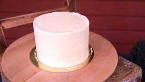 En vitchokladtårta som står ute på en stol på kylning.