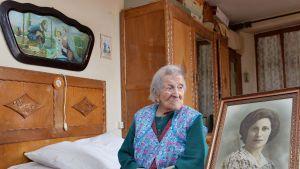 Emma Morano i hennes sovrum, intill ett ungdomsporträtt.