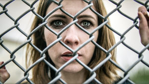 Huvudpersonen Linda i närbild bakom hönsnät på fängelsets gård i isländska tv-serien Fångar