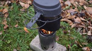 Puukaasukeittimellä kiehautetaan vettä pakissa.