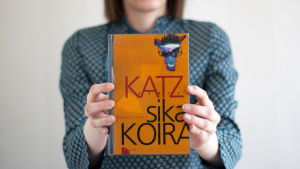Kirjabloggari Lukuisa Daniel Katzin kirja Saksalainen sikakoira käsissään