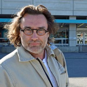 Erik Söderblom, ny chef för Esbo stadsteater, poserar framför Mediahuset.