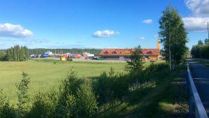 En grön äng och till höger skymtar en asfalterad väg. Längre bort synd en ABC-bränslestation samt parkerade långtradare. Blå himmel, solsken.