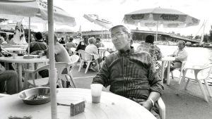 Arne Roms sitter på strandcaféts terrass, ån i bakgrunden, svartvit bild.