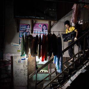 Begravningsentreprenörer bär kroppen av en droghandlare i Filippinerna den 14 juli i Manila.